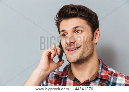 Closeup of happy young man talking on cell phone over grey background