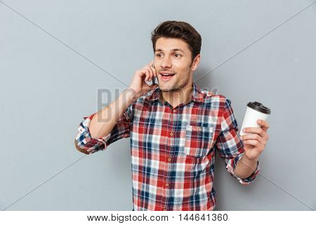 Hnadsome young man talking on cell phone and drinking takeaway coffee over grey background