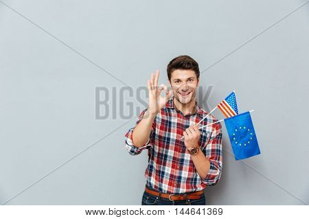 Cheerful young man with flags of Europe Union and United States showing ok sign over grey background
