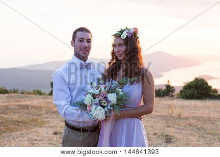 the bride and groom posing on the sunset with a wedding bouquet