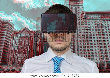 Young man is wearing virtual reality glasses. 3D simulation of city.