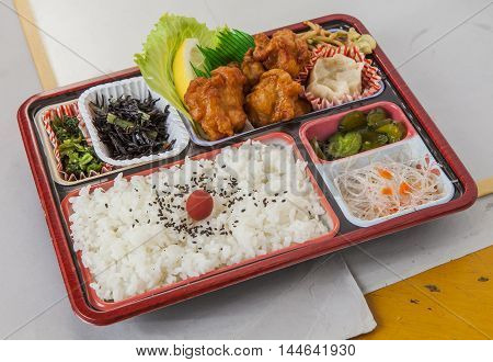 Faint fried chicken lunch with fried tempura chili and plain rice in bento box