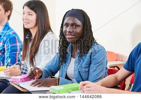 Happy african student smiling in class in university