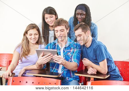 Happy students with tablet in their classroom at university