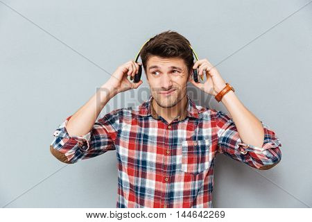 Confused unhappy young man in headphones listening to music over grey background