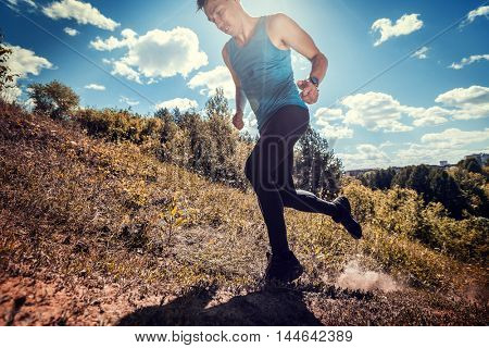 Athlete crossing off road terrain at sunny day