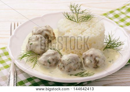 Veal meatballs with dill sauce and boiled rice .