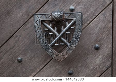 Doorknocker on the wooden gate fixed with rivets in Kokorin Castle in Central Bohemia, Czech Republic.