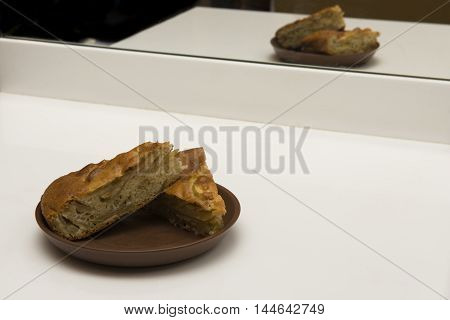 Two pieces of apple pie on a brown plate