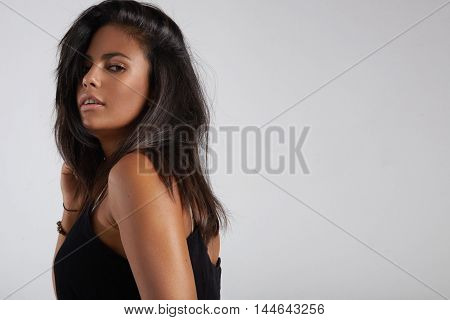 Spanish Woman With Healthy Shining Hair Watching At Camera From The Back