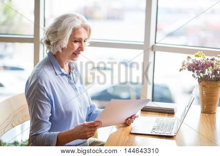 Life after retirement. Pleasant delighted senior woman sitting at th able and using laptop while resting in the cafe
