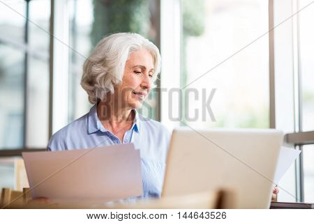 Involved in work. Pleasant aged delighted woman holding papers and using laptop while sitting at the table