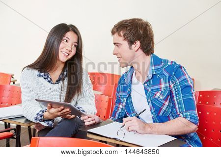 Two students flirting in school in a classroom with a tablet