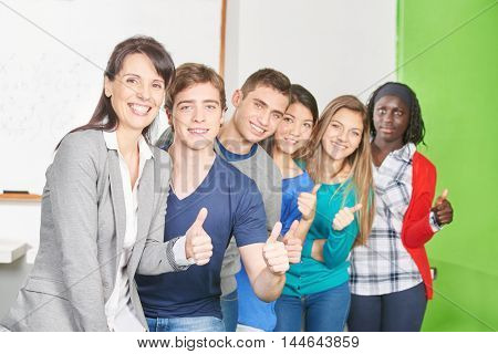 Teacher and students hold their thumbs up in a high school classroom