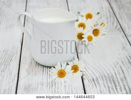 jug with milk and chamomile flower on a wooden table