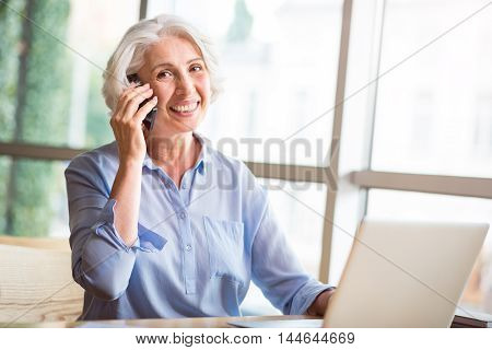 Glad to hear you. Joyful content senior woman smiling and talking on cell phone while sitting at the table