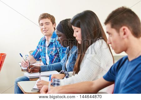 Smiling student takes a test in an interracial group