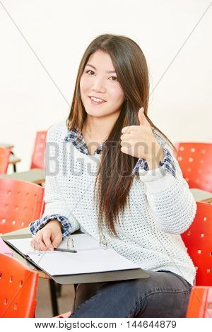 Asian women in class at her high school with thumbs up