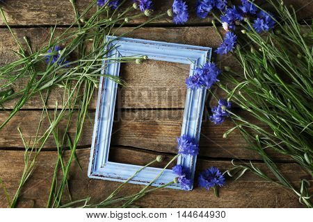 Retro frame with bluettes on wooden background, top view