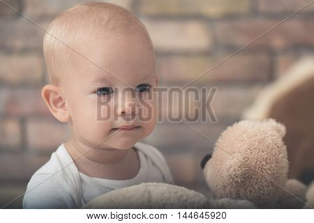 Cute child portrait, baby girl looking at plush animal