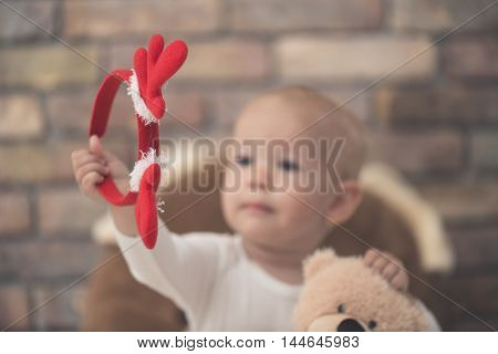 Cute child portrait, baby girl holding a christmas wreath