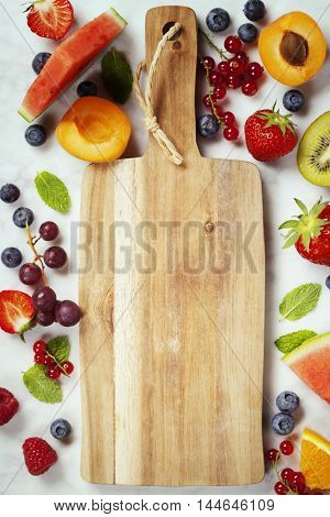 Old cutting board, Watermelon, berries, fruits and mint leaves on white marble background. Summer fruit concept.