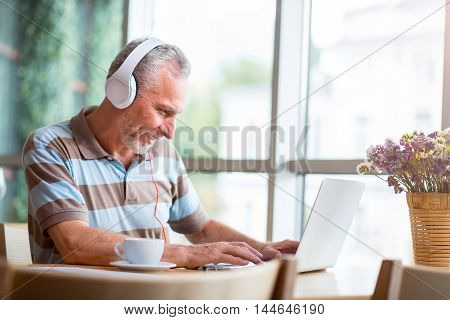 Modern advancements. Cheerful senior smiling man using laptop and listening to music while sitting at the table