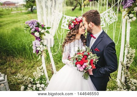 bride and groom outdoors. wedding ceremony. wedding arch.