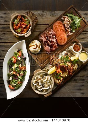Osia Steak Seafood Grill with clams shrimp octopus squid mussel salad bacon wasabi and cream on wooden table