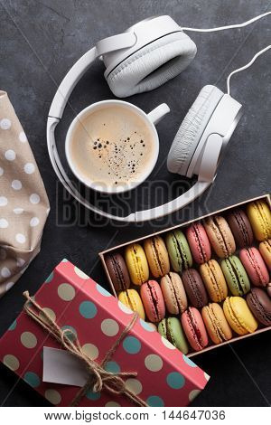 Colorful macaroons in a gift box and headphoned on stone table. Sweet macarons. Top view