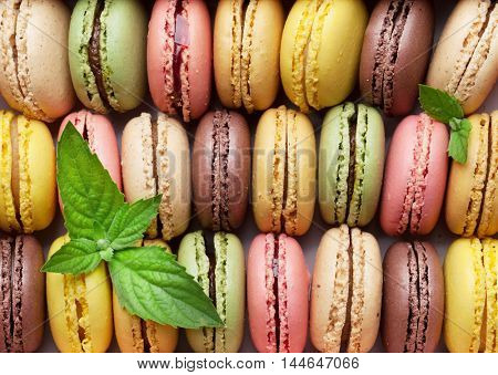 Colorful macaroons in a gift box with mint leaves. Sweet macarons and flowers. Top view
