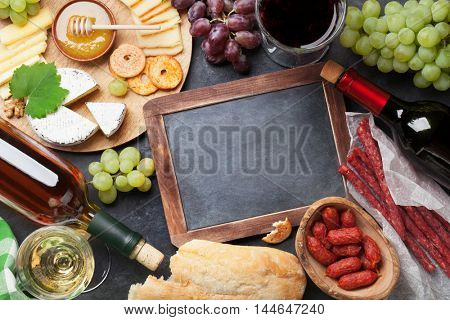 Red and white wine, grape, honey, cheese and sausages over stone table. Top view with blackboard for copy space