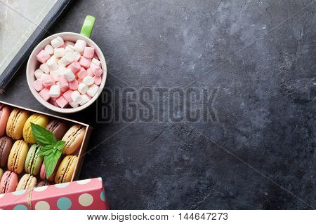 Colorful macaroons in a gift box and marshmallow in coffee cup on stone table. Sweet macarons. Top view with copy space