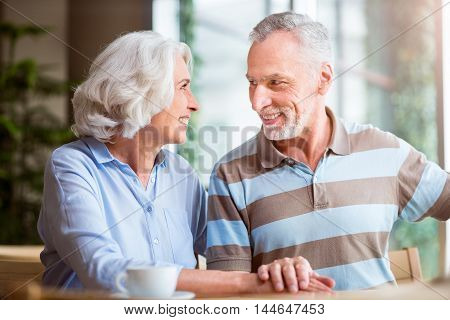 Love you so much Positive smiling senior couple looking at each other and sitting at the table while resting together