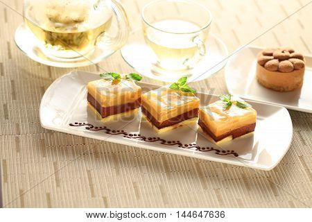 Pudding cake with mint leaves on white plate with tea