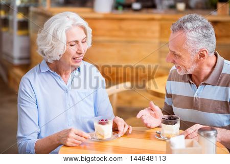 Bon appetit. Cheerful senior loving couple sitting at the table and having a meal while resting in the cafe
