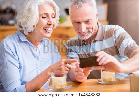Full of emotions. Cheerful senior loving couple sitting at the table and having meal while using cell phone