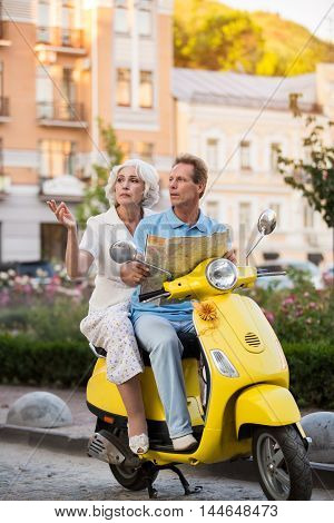 Mature couple sitting on scooter. Man holds a map. How should we navigate. First time to this city.