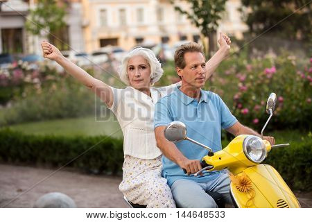 Mature couple on a scooter. Woman with raised hands. Go on a trip together. Feeling of freedom.