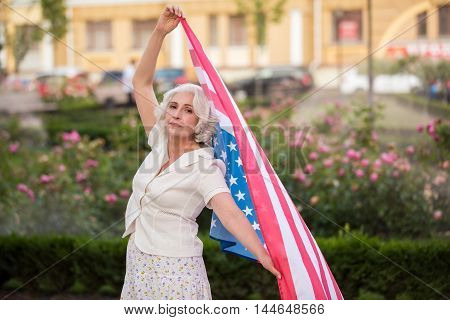 Mature woman holds USA flag. Banner of America. Pride of the citizen. Stay free and live long.
