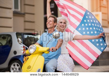Mature couple riding yellow scooter. Woman raises USA flag. Love and pride. Warm hearts and bright smiles.