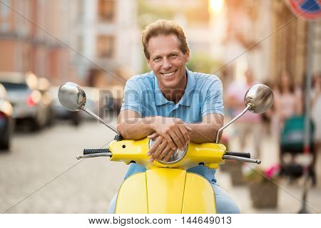 Mature guy is smiling. Man sits on yellow scooter. Spend your free time actively. Tourist in the city.