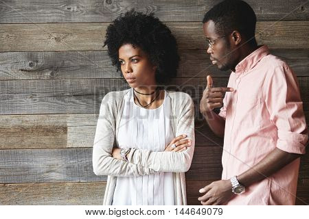 Dark-skinned Man Standing Next To His Offended Wife With Afro Haircut And Crossed Arms, Man Looking
