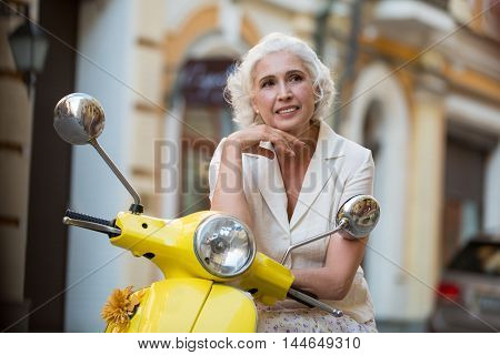 Mature woman leans on scooter. Lady is smiling kindly. Let the dreams come true. Place I've never been to.