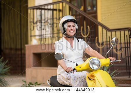 Lady on scooter wearing helmet. Female scooter driver is smiling. Ride and explore the city. Vacation during summertime.