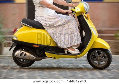 Woman riding on a scooter. Yellow scooter on the road. Decrease speed to save fuel. Long way home.
