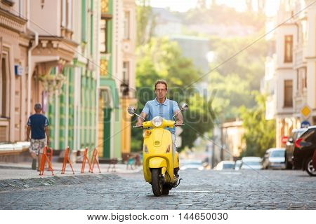 Mature guy riding yellow scooter. Scooter on the road. Quickly travelling around the city. Speed and comfort.