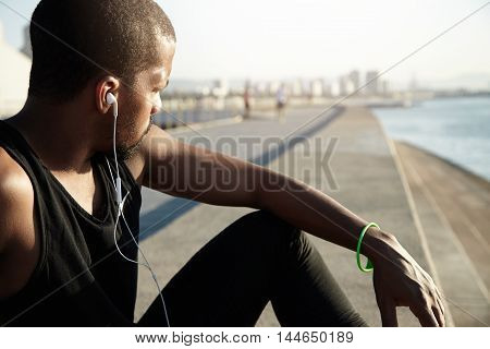 Cropped Portrait Of Young African Man With Muscular Body Wearing Earphones While Resting Alone On Em