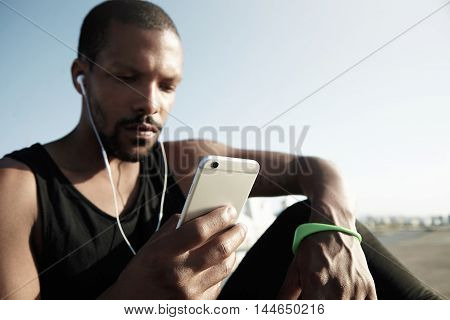 Portrait Of Pensive Handsome Dark-skinned Man With Little Beard Listening To Music On His Smartphone