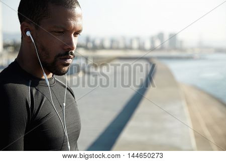 Pensive African American Athlete Listening To Music In White Headphones. Thoughtful Man Brooding Upo